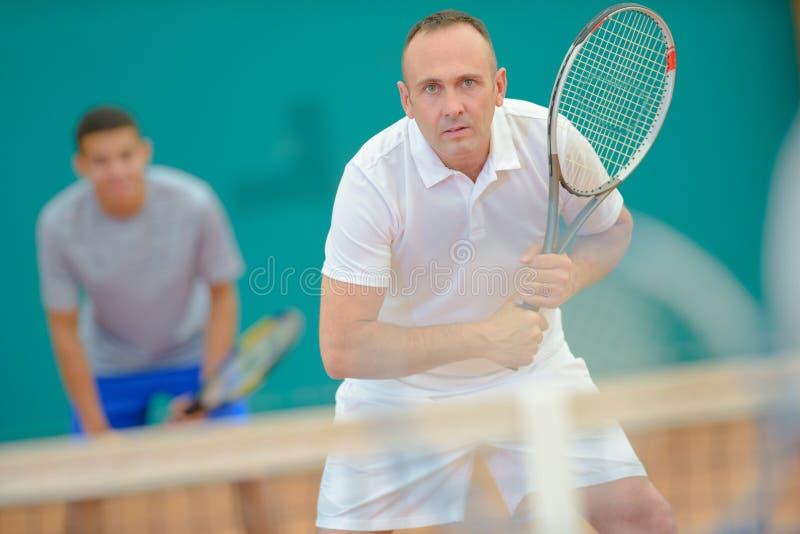 Men playing doubles tennis. Tennis royalty free stock photos