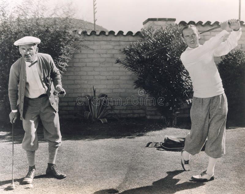 Men playing golf in backyard royalty free stock images