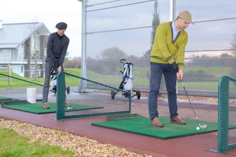 Men playing golf in golf course stock photos