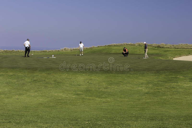 Men playing golf putting green royalty free stock photography