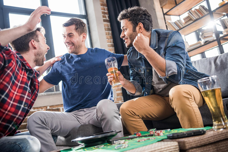 Men playing roulette game. Excited young men playing roulette game. young people having fun concept royalty free stock images