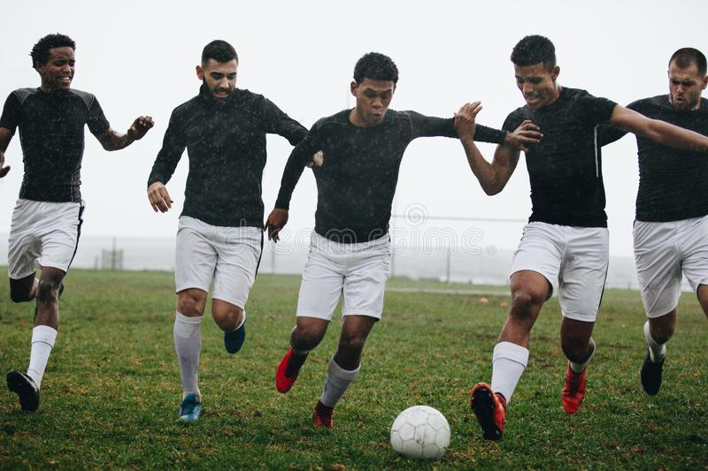 Men playing soccer running after a football on a rainy morning. Footballers trying to take possession of the ball running on the royalty free stock photography