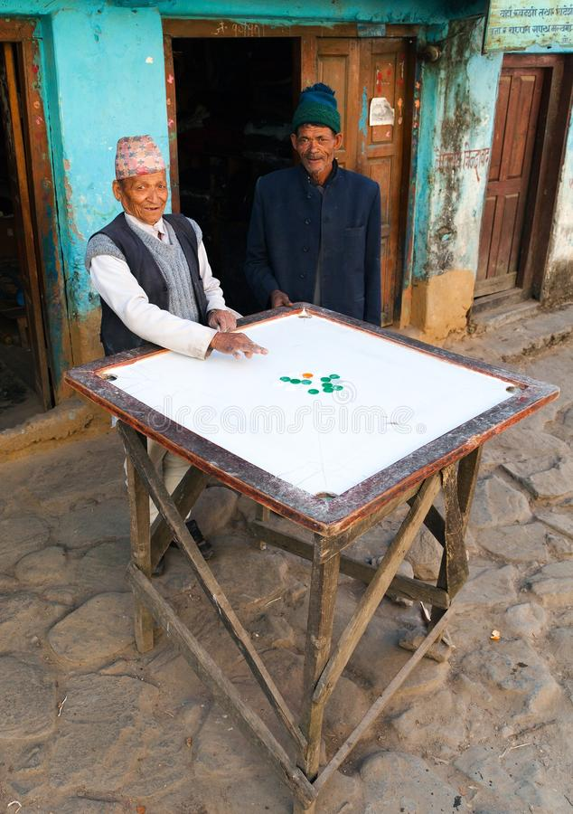 Men playing typical nepalese desk game Carryam board stock photography