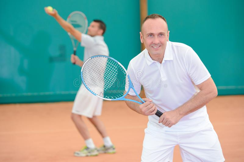 Men playng tennis doubles. Man royalty free stock photo