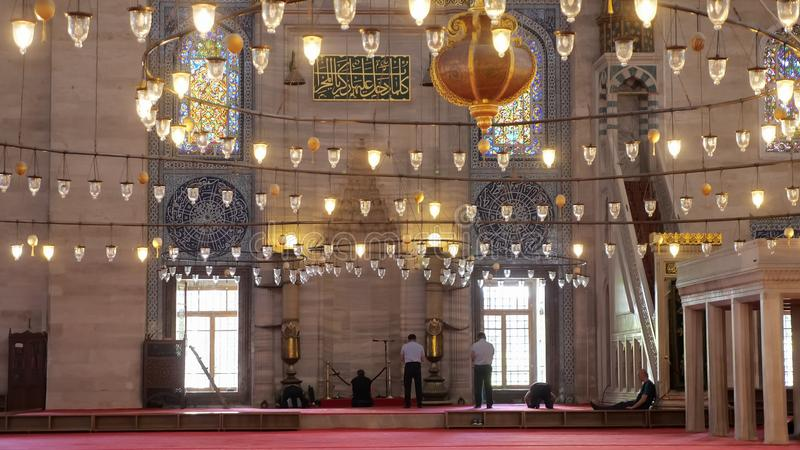 Men pray in mosque decorated with lanterns in Istanbul stock images