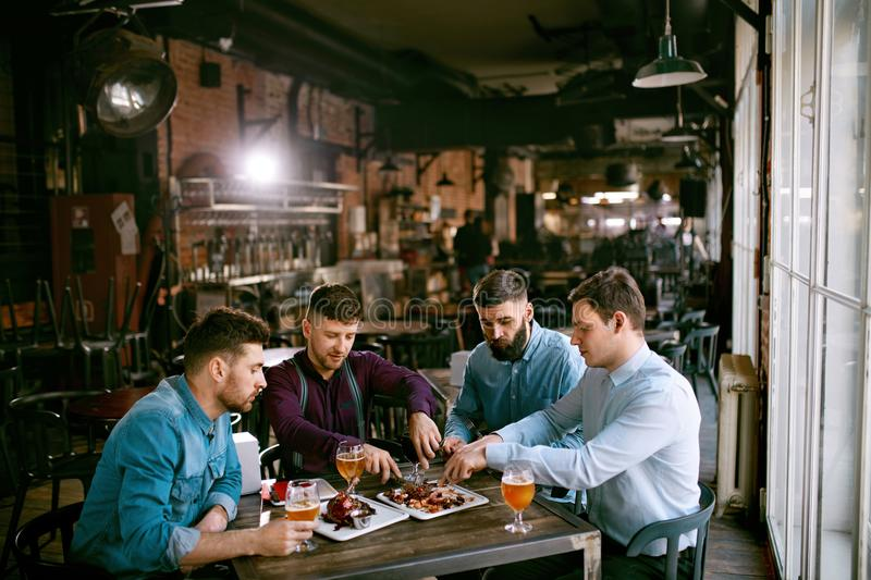Men In Pub Drinking Beer And Eating Food. Friends Having Dinner. High Resolution royalty free stock photo