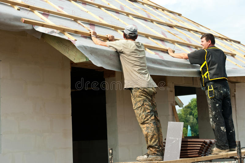 Men putting roof on a house royalty free stock photography