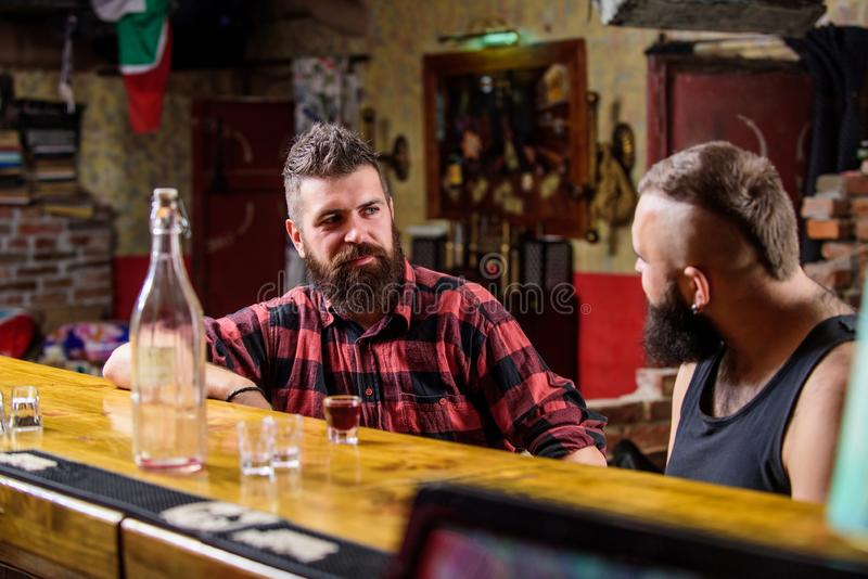 Men relaxing at bar. Strong alcohol drinks. Friday relaxation in bar. Friends relaxing in bar or pub. Interesting royalty free stock photography