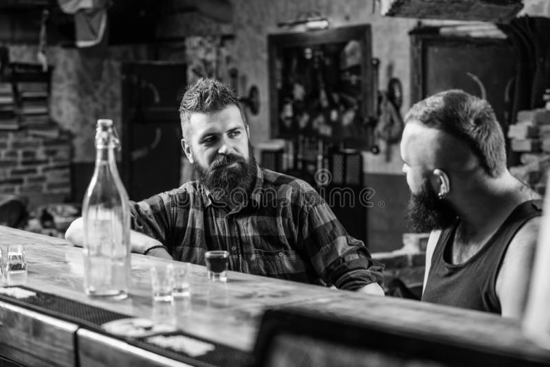 Men relaxing at bar. Strong alcohol drinks. Friday relaxation in bar. Friends relaxing in bar or pub. Interesting. Conversation. Hipster brutal bearded men stock images