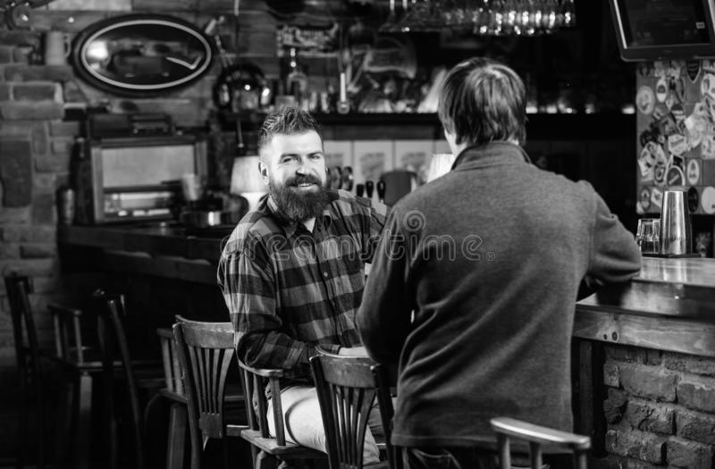 Men relaxing in pub. Weekend leisure. Friday relaxation in pub. Friends relaxing in pub. Friendly conversation with. Stranger. Hipster brutal bearded men spend royalty free stock photos