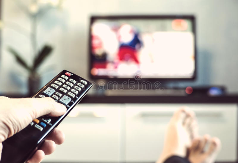 Men with the remote control, front of the television. royalty free stock photos