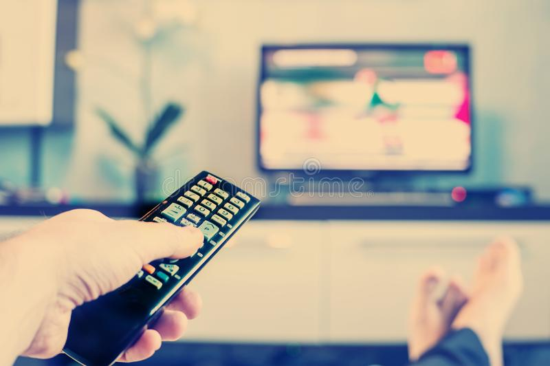 Men with the remote control, front of the television. royalty free stock photo