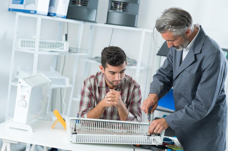 Men repairing electric heater. Men repairing an electric heater stock photo