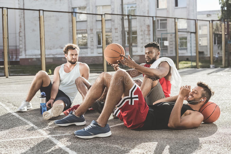 Men resting after basketball game on court. Multiethnic group of men resting after basketball game on court stock photography