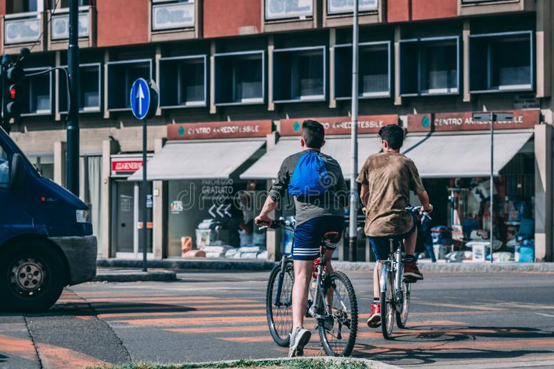 Men Riding Bicycles Traveling on Road Near Red and Gray Building royalty free stock photography