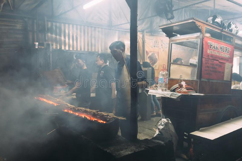 Men Roasting meat, chicken and mutton satays with charcoal, fire and smoke at night market in Jakarta, Indonesia. stock photos