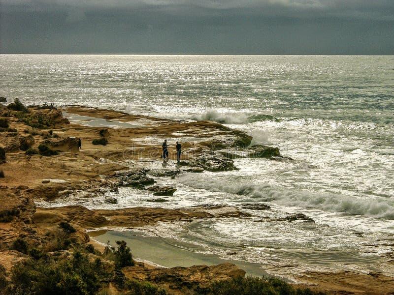 Men on rocky beach in Mediterranean stock photos