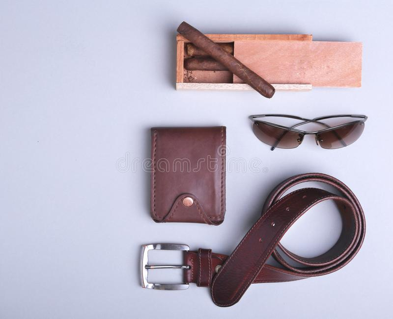 Men`s accessories for business and recreation. Wallet, belt, glasses, cigar. Top view composition. Men`s accessories for business and recreation. Wallet, belt stock image
