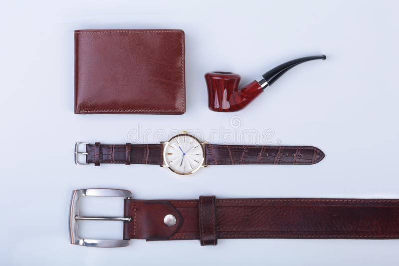 Men`s accessories for business and rekreation. Leather belt, wallet, watch and smoking pipe on white background.. Top. View composition stock images