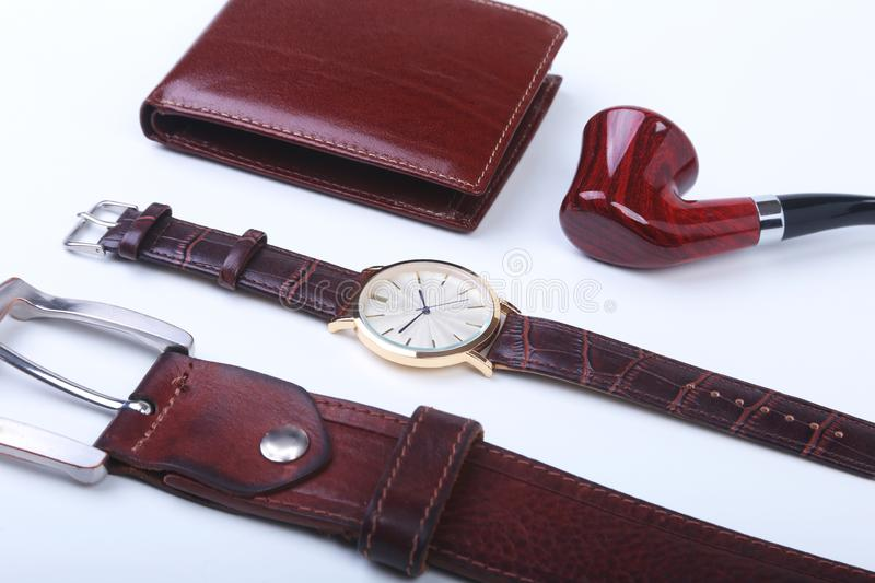 Men`s accessories for business and rekreation. Leather belt, wallet, watch and smoking pipe on white background.. Top. View composition royalty free stock image
