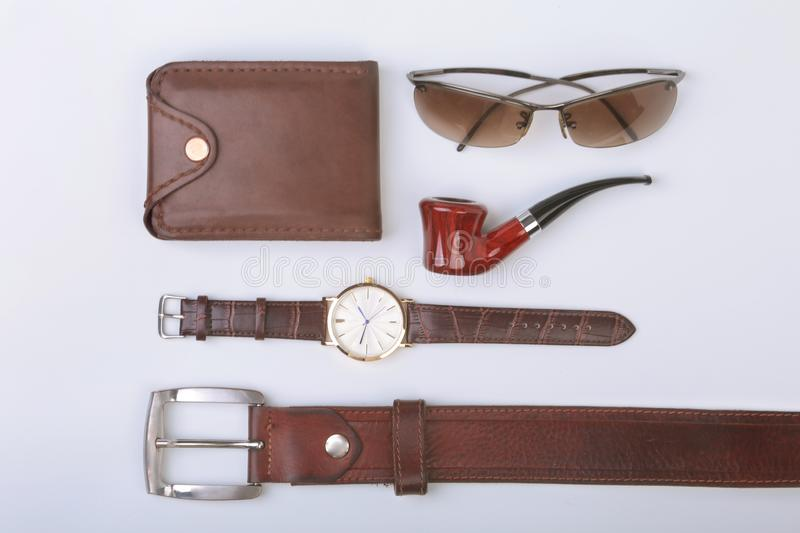 Men`s accessories for business and rekreation. Leather belt, wallet, watch and smoking pipe on white background.. Top. View composition stock photo