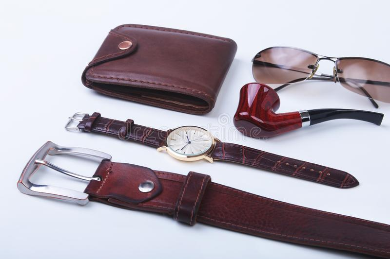 Men`s accessories for business and rekreation. Leather belt, wallet, watch and smoking pipe on white background.. Top. View composition royalty free stock photos