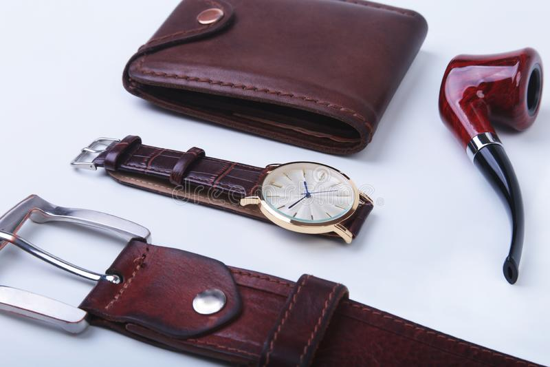 Men`s accessories for business and rekreation. Leather belt, wallet, watch and smoking pipe on white background.. Top. View composition stock image