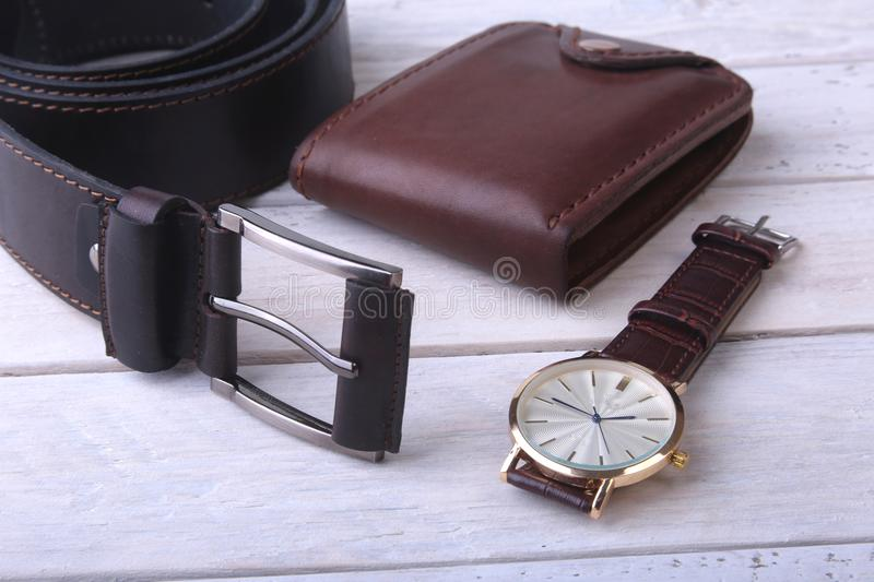 Men`s accessories for business and rekreation. Leather belt, wallet, watch and smoking pipe on wood background.. Top. View composition stock images