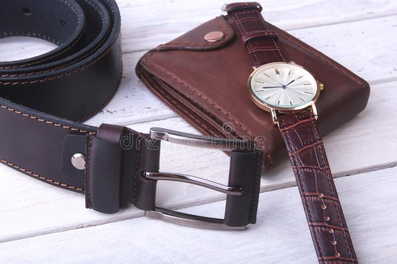 Men`s accessories for business and rekreation. Leather belt, wallet, watch and smoking pipe on wood background.. Top. View composition royalty free stock images