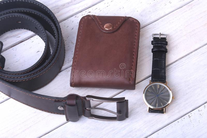 Men`s accessories for business and rekreation. Leather belt, wallet, watch and smoking pipe on wood background.. Top. View composition royalty free stock photography