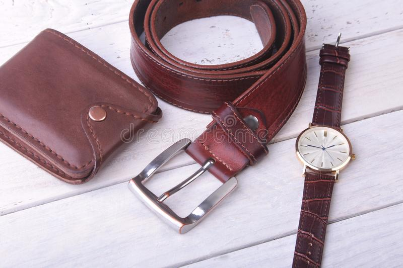 Men`s accessories for business and rekreation. Leather belt, wallet, watch and smoking pipe on wood background.. Top. View composition stock image