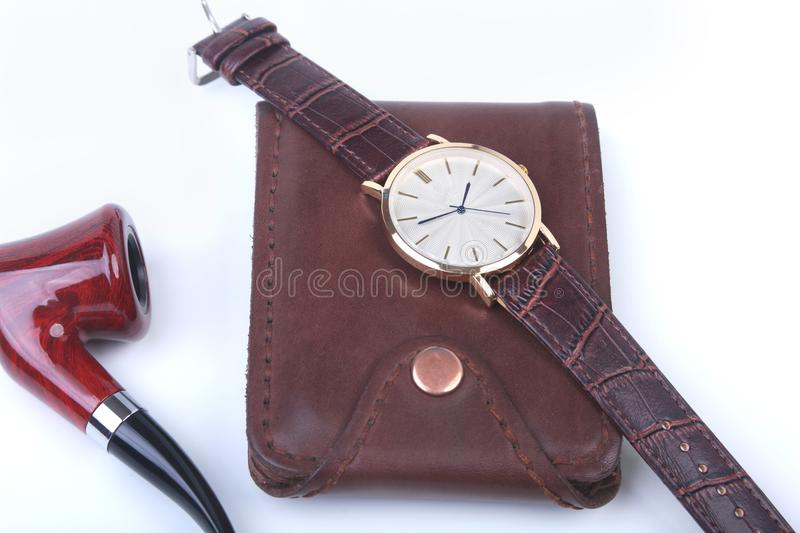 Men`s accessories for business and rekreation. Leather wallet, watch and smoking pipe on white background.. Top view. Composition royalty free stock photography