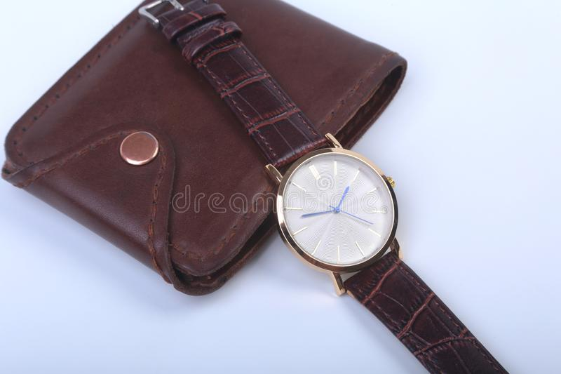 Men`s accessories for business and rekreation. Leather wallet, watch and smoking pipe on white background.. Top view. Composition stock images
