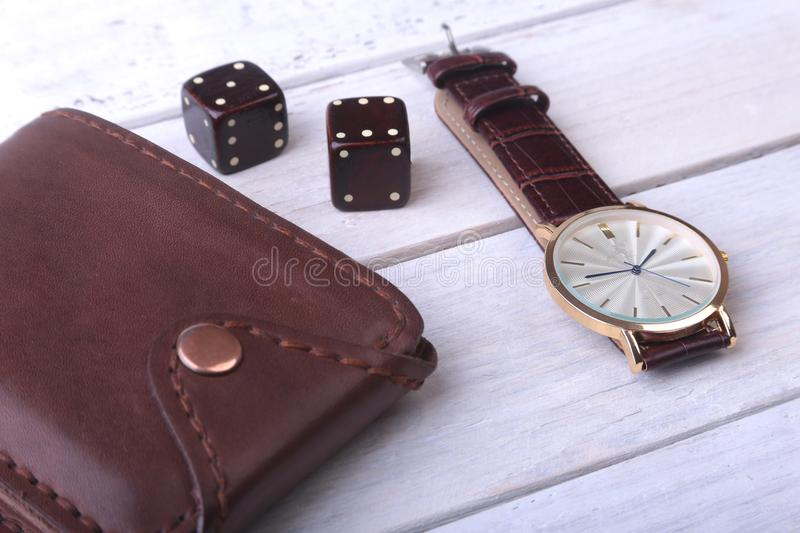 Men`s accessories for business and rekreation. Watch, leather wallet and dice on wood background.. Top view composition. Men`s accessories for business and stock photos