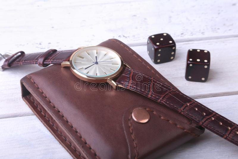 Men`s accessories for business and rekreation. Watch, leather wallet and dice on wood background.. Top view composition. Men`s accessories for business and royalty free stock photography