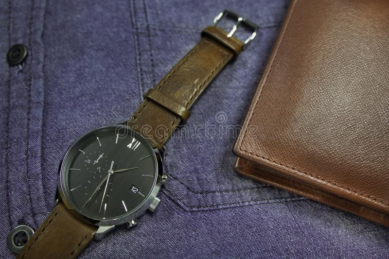 Men`s accessories classic and luxury watch brown leather strap with wallet on blue jean shirt. for life stlye, elegant to dress o stock image