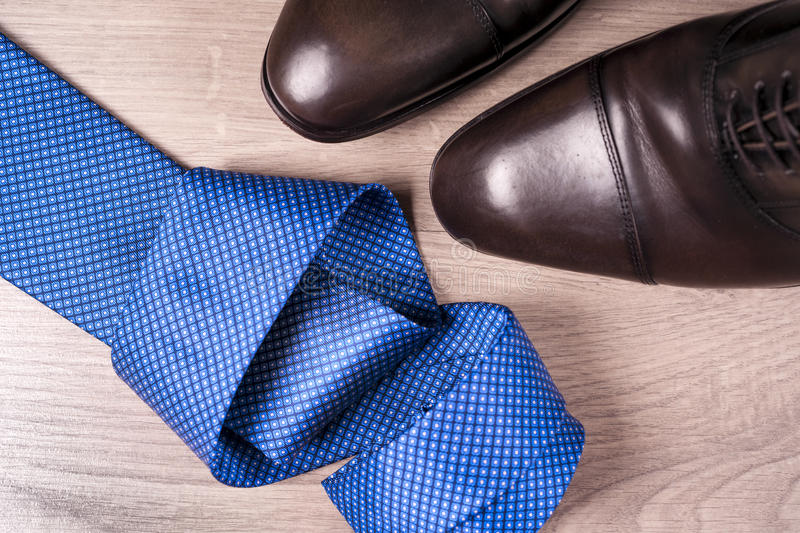 Men`s accessories men`s shoes, tie on a wooden background. Classic men`s accessories. Top view royalty free stock images