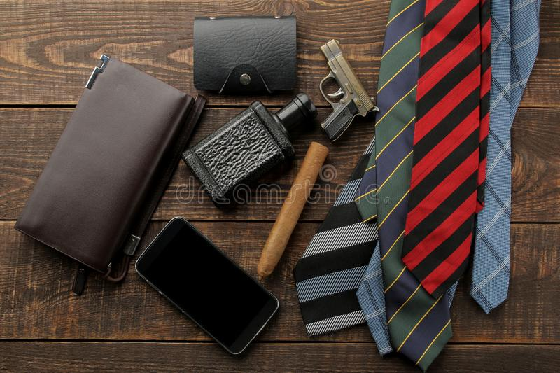 Men`s Accessories. men`s style. ties, smartphone, perfume, wallet, business card on a brown wooden background. flat lay royalty free stock image