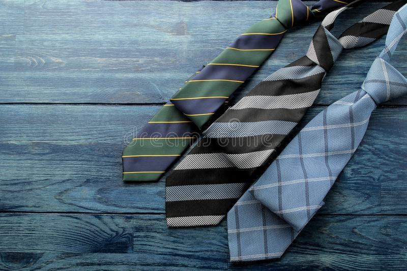 Men`s Accessories.men`s style. various ties on blue wooden background. flat lay. with space for text royalty free stock photography