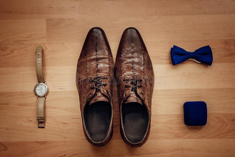 Men`s accessories: watch, tie, belt, cufflinks, perfume shoes top view royalty free stock photography