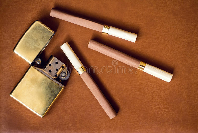 Men's accessory, golden lighter and cigarettes on royalty free stock photos