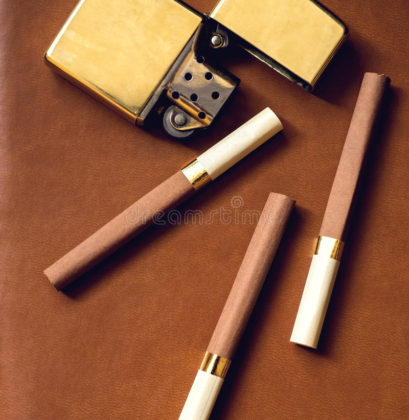 Men's accessory, golden lighter and cigarettes on stock photo