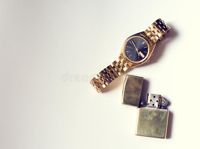 Men's accessory, golden watch and lighter on white stock image