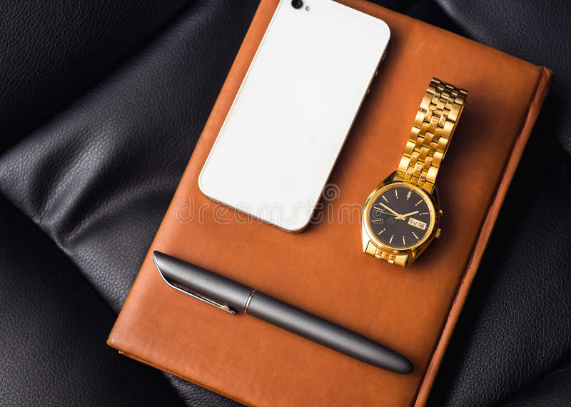Men's accessory, golden watch, pen and mobile phone on the leather diary. Men's accessory, golden watch, pen and mobile phone on the leather diary stock images