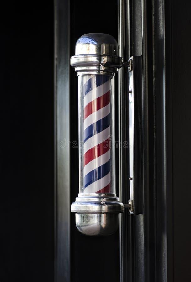 Men's barber hair dressing shop pole sign. Men's barber hair dressing shop traditional outdoor pole sign helical stripe stock photography