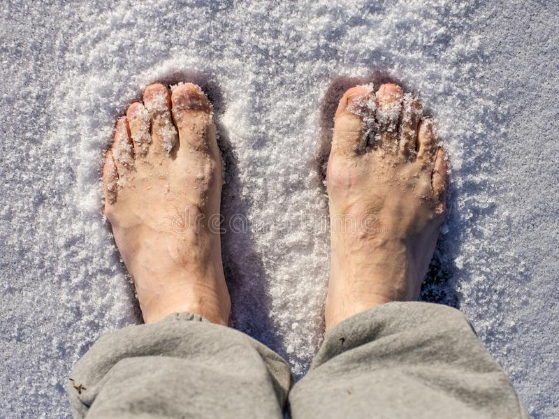 Men`s bare feet in the snow in a sunny day. royalty free stock photo