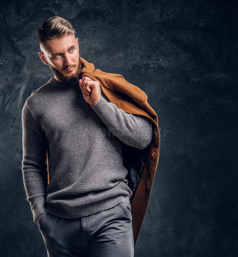 Men`s beauty, seasonal fashion. Portrait of a stylish male holding his demi-season coat. Studio photo against a dark stock image
