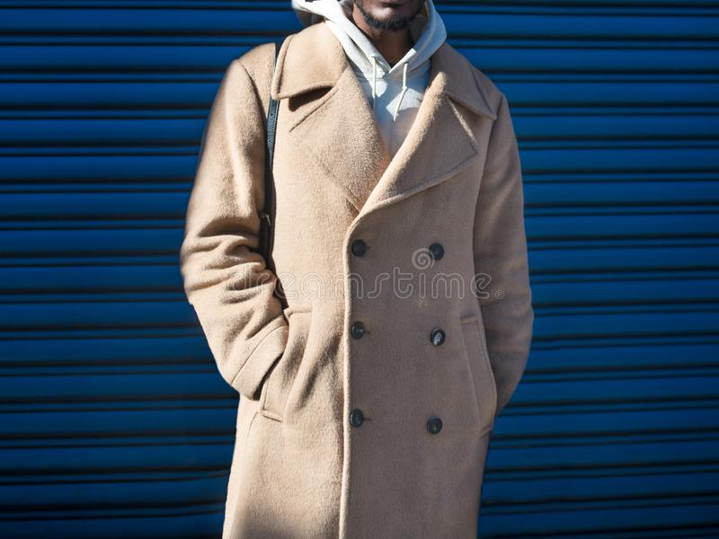 Men`s beige cashmere wool jacket on male model posing near blue wall in the city street. stock photography