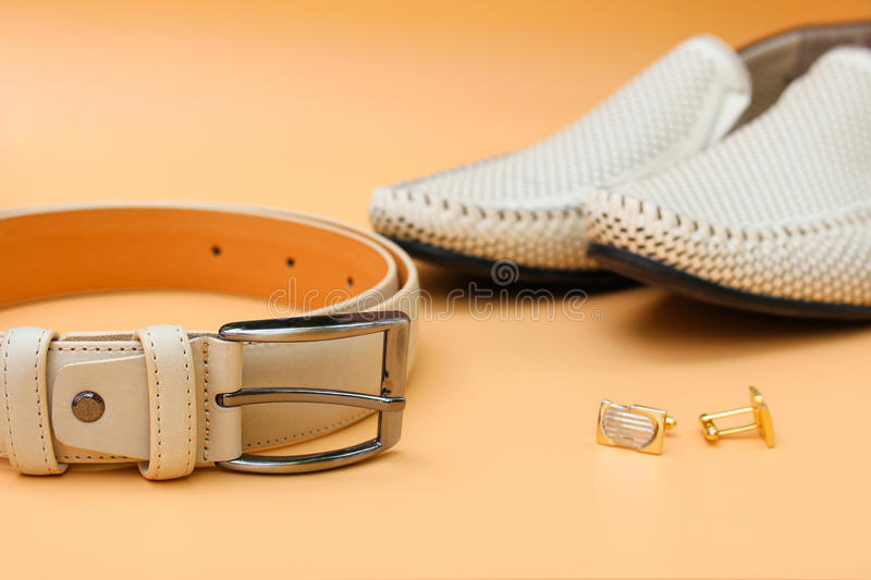 Men`s belt, shoes, cufflinks. On beige background royalty free stock photos