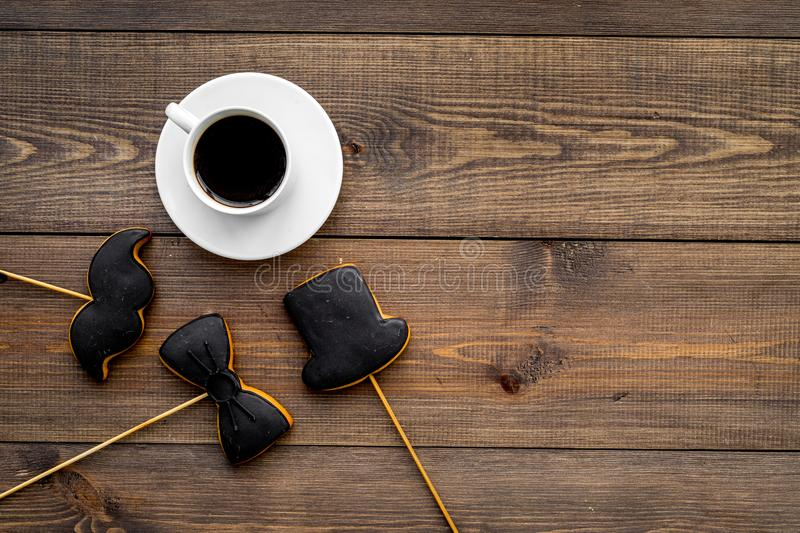 Men`s birthday celebration concept. Cookies in shape of moustache, hat, bow tie near coffee on dark wooden background royalty free stock photo